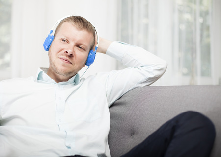 Young man smiling to himself as he listens to music on his headphones while relaxing on a sofa at home staring off into the air with a contented expression