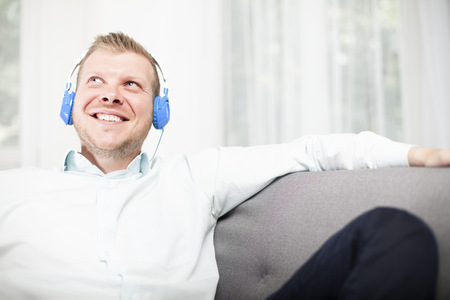 Happy man smiling as he listens to his music on a set of headphones while relaxing on a comfortable sofa at home looking up into the air with a beaming smile of enjoyment photo