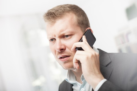 Anxious businessman taking a mobile phone call frowning with a worried expression as he listens to the conversation