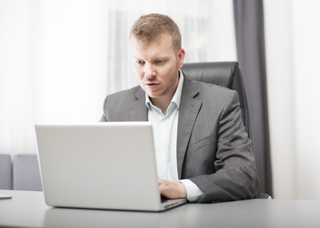 Businessman looking at his laptop in disbelief with a puzzled shocked expression as he digests the information on the screen