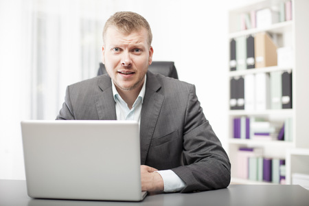 Attractive young businessman sitting at his desk in the office listening intently to the viewer leaning forward with an attentive expression on his face photo