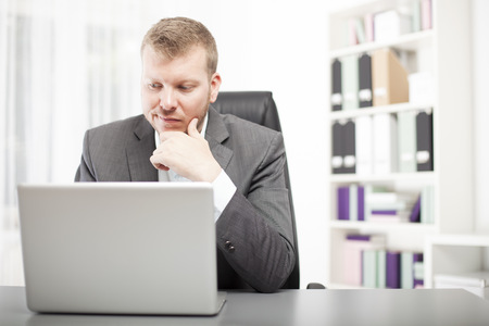 wry: Businessman sitting at his desk in the office looking at his laptop with a wry expression grimacing as he reads information on the screen