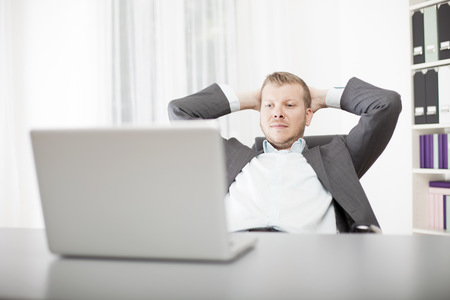 Successful confident young businessman sitting back in his chair at the office with his hands clasped behind his head and a satisfied expression photo