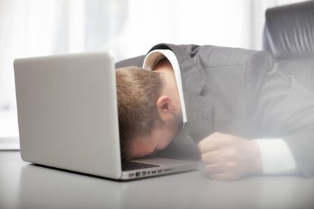 banging: Desperate depressed businessman banging his fist on his desk and resting his head on the keyboard of his laptop computer Stock Photo
