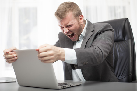 Angry businessman shaking his laptop computer and yelling in fury as he sits at his desk in the office