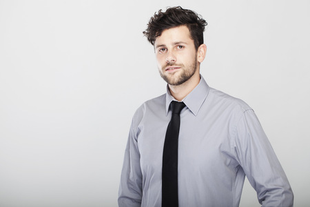 confident modern stylish young and trendy business man, pose in front of grey background. Stock Photo