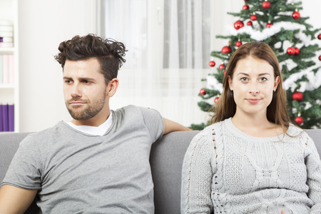 young modern couple is irritated of christmas with christmas tree Stockfoto