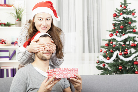 young girl is giving her boyfriend a christmas gift in front of christmas tree