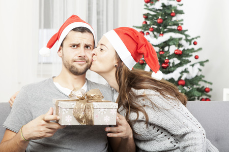 sceptical: man is sceptical about christmas gift  while his girlfriend give him a kiss