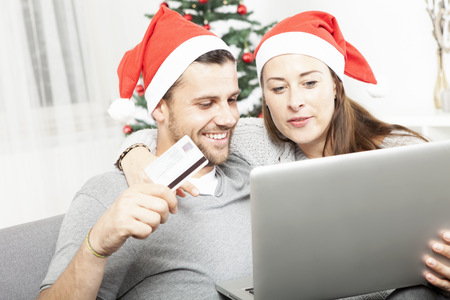 happy couple find perfect present gifts online on sofa indoors using credit card and laptop photo