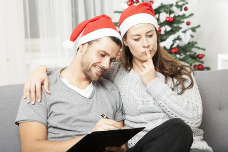 shopping list: happy young couple think about to do list for christmas eve on sofa