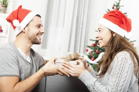 young man give her girlfriend a present box for christmas eve photo