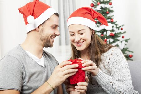 young couple opens christmas gift box and is happy in front of christmas tree photo