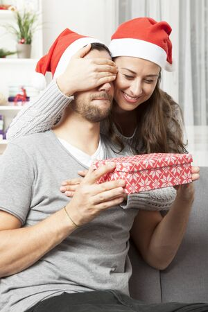 suprise: young happy girl suprise her boyfriend with christmas gift Stock Photo