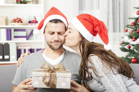 boyfriend looks sceptical to his christmas gift while his girlfriend give him a kiss
