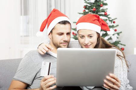 happy couple shopping online present gifts on sofa indoors using credit card photo