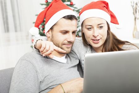 happy couple buying online presents on sofa indoors using credit card photo