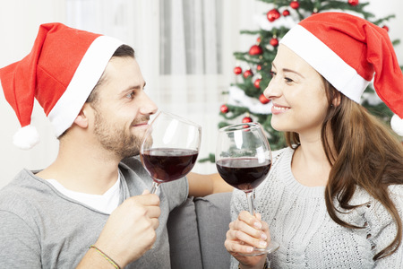 happy young couple enjoy chistmas with wine on sofa at home photo