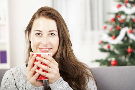 young happy girl enjoy hot coffee at christmas tree  photo
