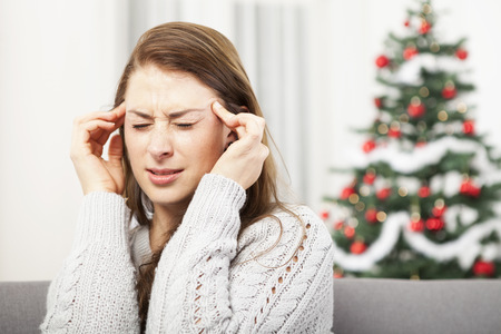 young unhappy girl has headache of christmas stress with tree in background photo