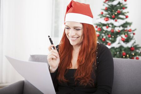 wishlist: young red hair girl writing a wish list and wearing a red santa hat in front of a firtree with lights and balls Stock Photo