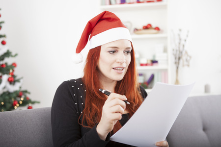 wishlist: young red hair girl writing a wish list and wearing a red santa hat in front of a fir tree with lights and balls, sitting on a sofa couch Stock Photo