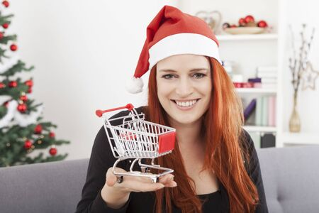 trolly: young happy christmas girl showing mini shopping trolly cart, for presents or gifts