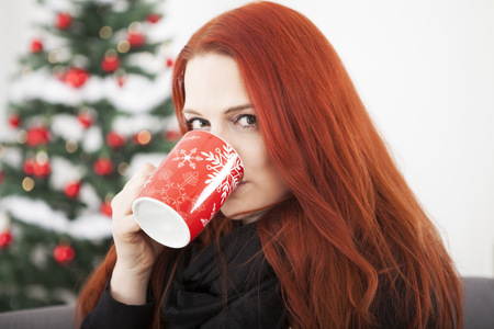 young red haired woman is drinking coffee or tea on christmas eve or winter morning photo