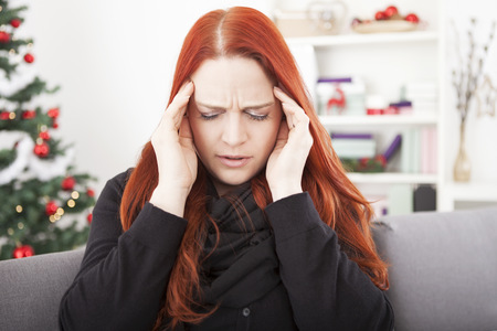 young red haired woman is sick and have headache on christmas Stockfoto