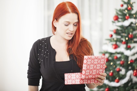 young red haired girl is really unhappy with gift box for christmas