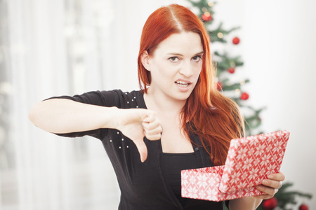 young red haired girl is really unhappy with gift box for christmas and thumbs down