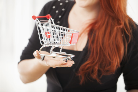 saleslady: close up of young happy girl with mini shopping cart trolley smiling