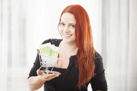 young happy girl with mini shopping cart trolley with euro bank note smiling photo