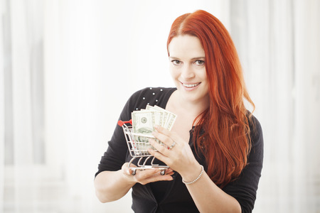 young happy girl with mini shopping cart trolley and dollar bank note smiling photo