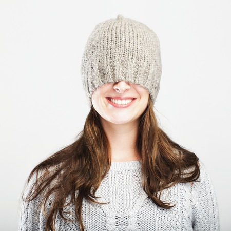 pull over: young happy playful cute winter girl covers eyes with hat, isolated on grey background