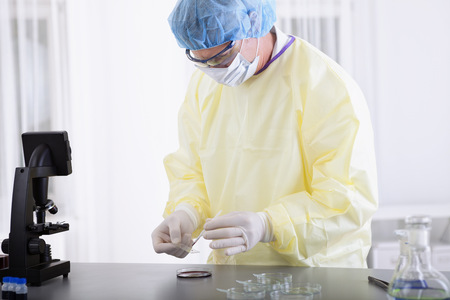 protective spectacles: portrait of scientist or doctor in protective gear working in lab or laboratory