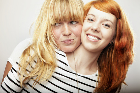 rode en blonde haired girls vrienden lachen en knuffel Stockfoto
