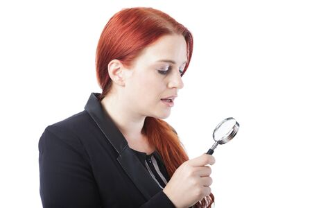 Attractive redhead woman holding a magnifying glass, profile view isolated on white in a conceptual image photo