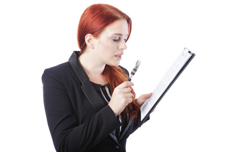 Close up Businesswoman with Burgundy Hair Reading a Report on Clipboard Using Magnifying Glass. Isolated on White Background. photo