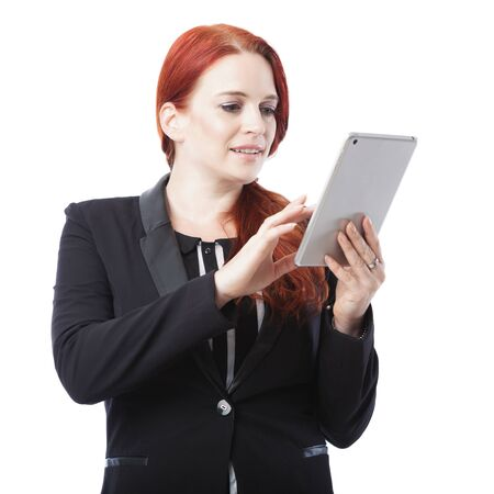 Attractive stylish young redhead businesswoman surfing the internet on her tablet computer navigating the touch screen with her finger, on white photo