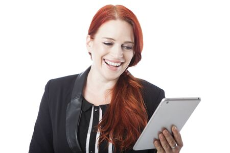 Stylish attractive redhead woman laughing with amusement as she reads her handheld tablet computer , upper body on white photo