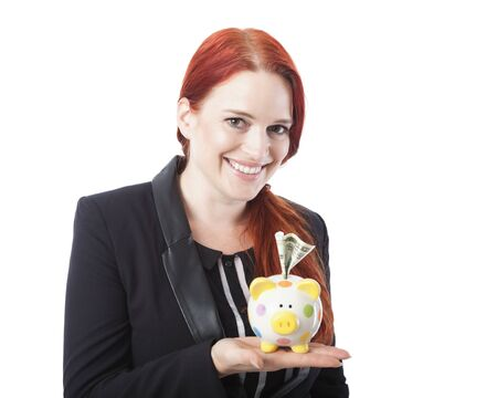 Pretty elegant redhead woman with a piggy bank balanced on her hand with a dollar note stuck in the slot looking at the camera with a charming warm smile, on white photo