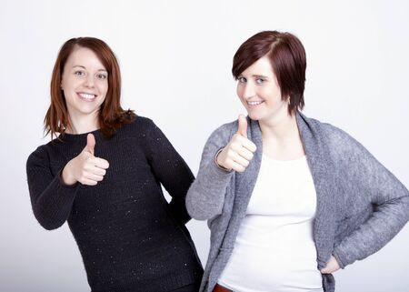 Two smiling young girls friends gesturing thumb up, isolated on grey background. photo