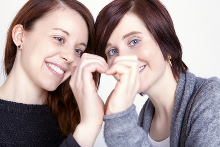 two girls friends make a heart with her hands on grey background photo