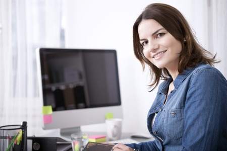 Close up Happy Adult Businesswoman Sitting at her Office Desk with Computer, Looking at the Camera.