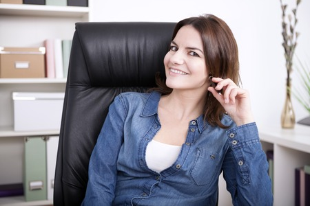 chilling: Happy Young Adult Businesswoman Sitting on her Chair with Hand on her Hair and Looking at the Camera. Stock Photo