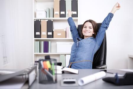 Giovane donna felice ufficio seduto sulla sua sedia allunga le sue braccia mentre guardando la fotocamera.