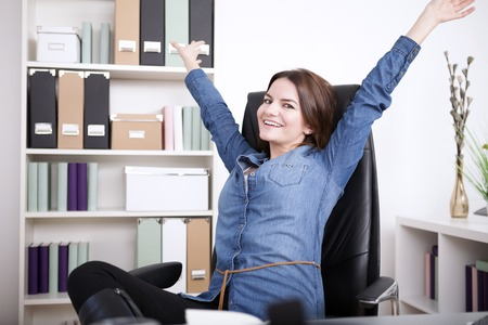 extending: Happy Office Woman in Denim Blouse Sitting on her Office Chair While Extending her Arms and Looking at the Camera.