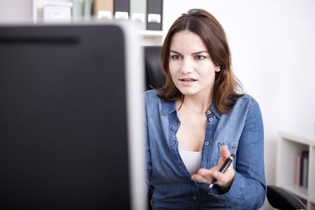 Close up Office Woman in Denim Clothing Looking at Computer Screen with Palm Up, Emphasizing Wondering Expression.
