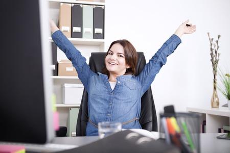그녀의 팔을 스트레칭하고 카메라를 찾고있는 동안 행복 여성 임원은 그녀의 사무실에서 의자에 앉아.